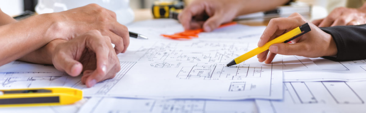 Group of people looking at plans on a table